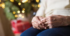 Elderly Hands in Front of Christmas Tree